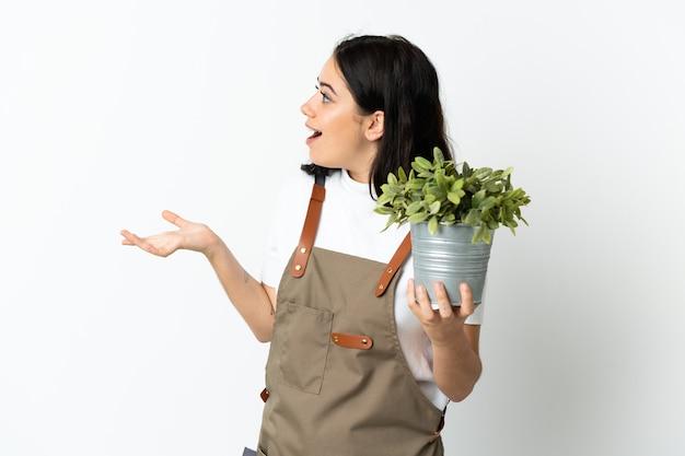 Giovane donna caucasica che tiene una pianta isolata