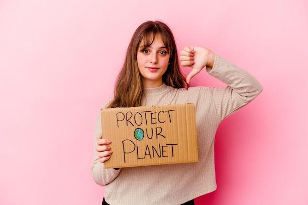 Giovane donna caucasica in possesso di un cartello proteggi il nostro pianeta isolato che mostra un gesto di antipatia, pollice in giù. concetto di disaccordo.
