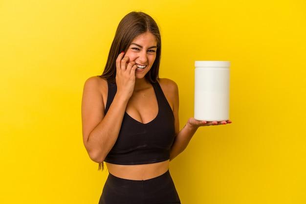 Giovane donna caucasica che tiene in mano una bottiglia di proteine isolata su sfondo giallo che si morde le unghie, nervosa e molto ansiosa.