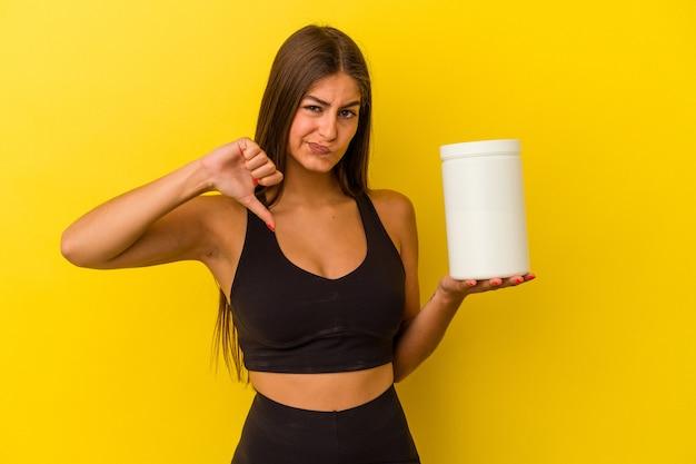 Giovane donna caucasica che tiene una bottiglia di proteine isolata su sfondo giallo che mostra un gesto di antipatia, pollice verso. concetto di disaccordo.
