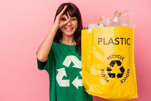 La giovane donna caucasica che tiene un sacchetto di plastica riciclato isolato sulla parete rosa ha eccitato mantenendo il gesto giusto sull'occhio.