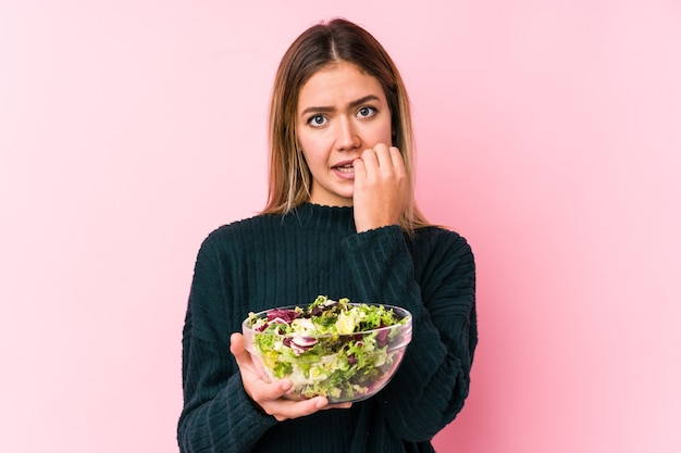 La giovane donna caucasica che tiene un'unghia mordace isolata insalata, nervosa e molto ansiosa.