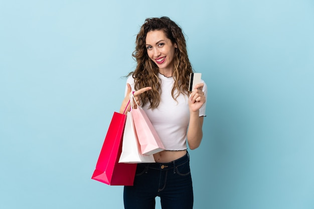 Giovane donna caucasica che tiene i sacchetti della spesa e una carta di credito