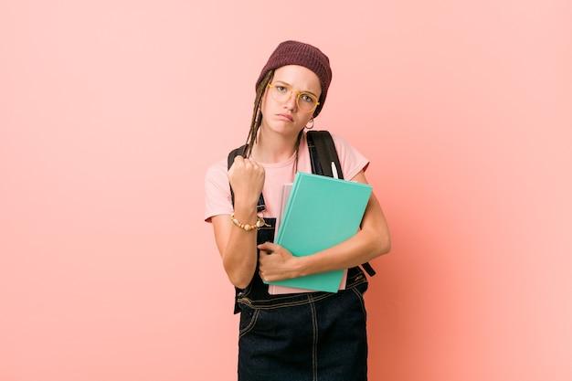 Giovane donna caucasica che tiene alcuni taccuini che mostrano il pugno alla macchina fotografica, espressione facciale aggressiva.