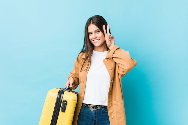 Giovane donna caucasica che tiene una valigia che mostra il segno di vittoria e che sorride ampiamente.