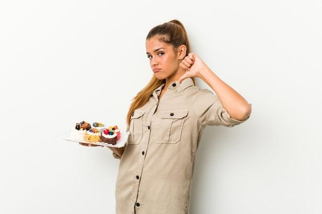 La giovane donna caucasica che tiene torte dolci si sente orgogliosa e sicura di sé, esempio da seguire.