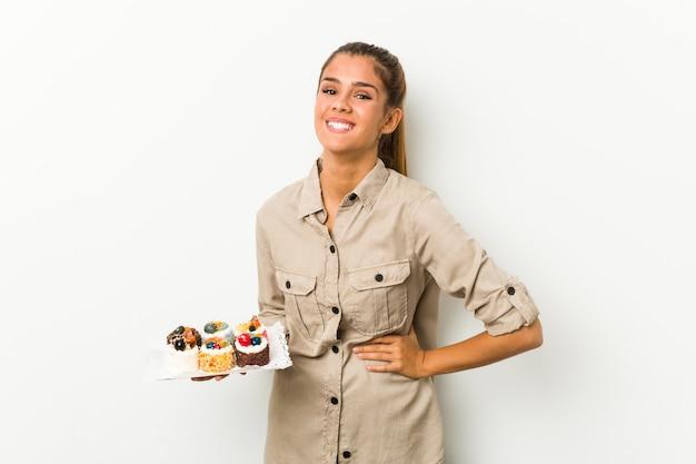 Giovane donna caucasica che tiene torte dolci ridendo e divertendosi.