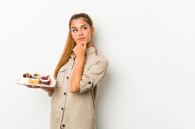 Giovane donna caucasica che tiene torte dolci guardando lateralmente con espressione dubbiosa e scettica.