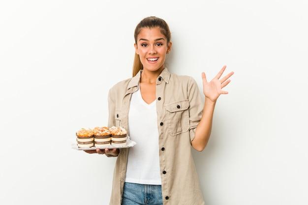 Giovane donna caucasica che tiene torte dolci che ricevono una piacevole sorpresa