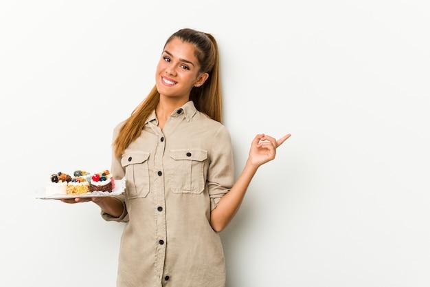Giovane donna caucasica che tiene torte dolci sorridendo e indicando da parte, mostrando qualcosa in uno spazio vuoto.
