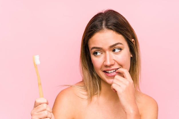 La giovane donna caucasica che tiene uno spazzolino da denti ha isolato il pensiero rilassato a qualcosa che guarda uno spazio della copia.