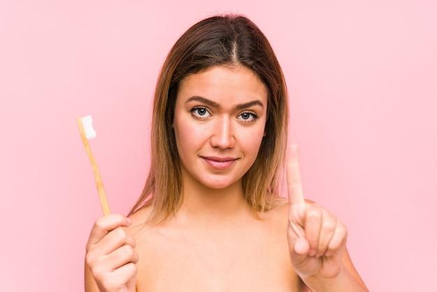 Giovane donna caucasica che tiene uno spazzolino da denti isolato che mostra il numero uno con il dito.