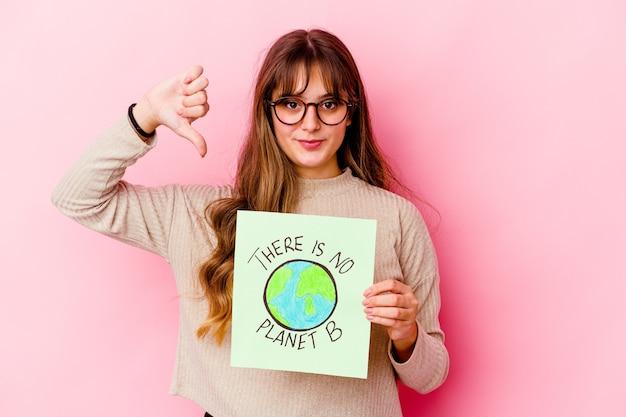 Giovane donna caucasica che tiene a non c'è il pianeta b isolato che mostra un gesto di antipatia, pollice in giù. concetto di disaccordo.