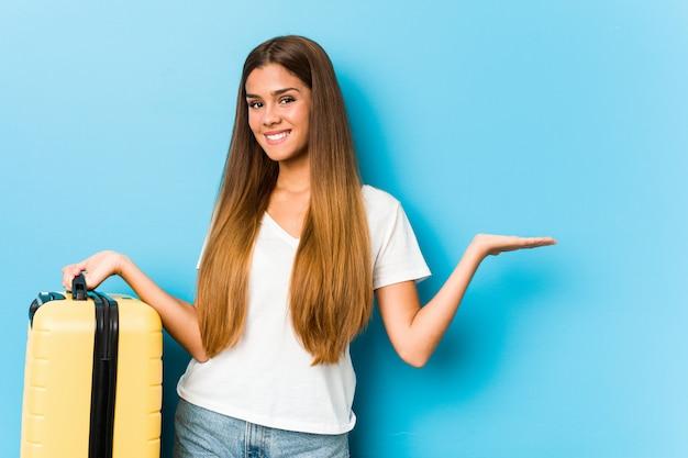 Giovane donna caucasica che tiene una valigia di viaggio che mostra uno spazio della copia su una palma e che tiene un'altra mano sulla vita