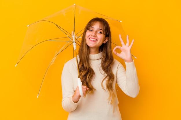 La giovane donna caucasica che tiene un ombrello ha isolato allegro e sicuro che mostra gesto giusto.