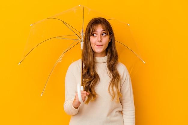La giovane donna caucasica che tiene un ombrello isolato confusa, si sente dubbiosa e insicura.