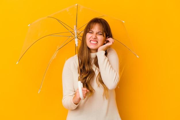 Giovane donna caucasica che tiene un ombrello isolato che copre le orecchie con le mani.