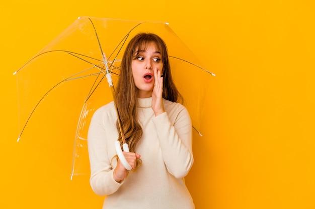 La giovane donna caucasica che tiene un ombrello isolato sta dicendo una notizia di frenata calda segreta e sta guardando da parte