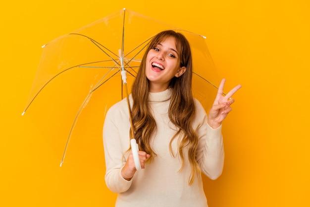 Giovane donna caucasica che tiene un ombrello isolato gioioso e spensierato che mostra un simbolo di pace con le dita.