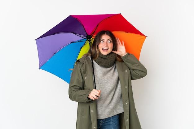 Giovane donna caucasica che tiene un ombrello isolato su bianco ascoltando qualcosa mettendo la mano sull'orecchio