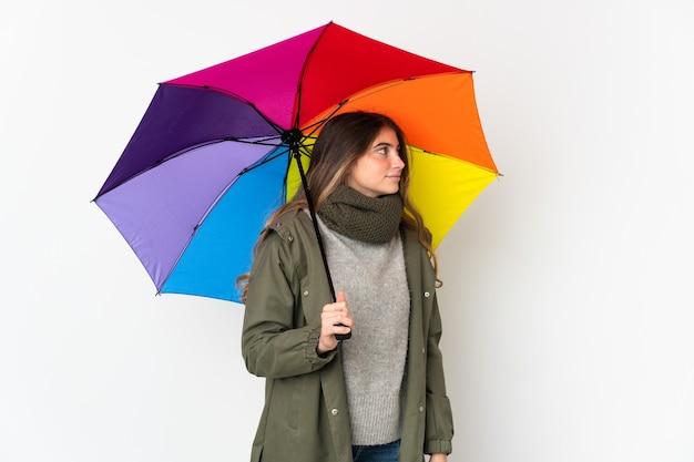 Giovane donna caucasica che tiene un ombrello isolato su bianco che osserva al lato