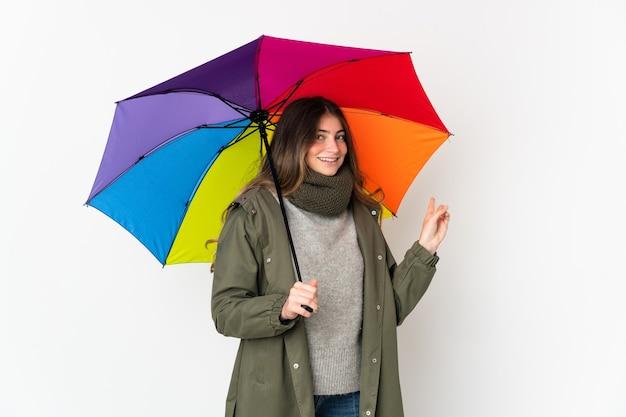 Giovane donna caucasica che tiene un ombrello isolato
