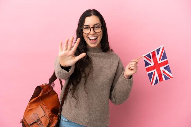 Giovane donna caucasica che tiene una bandiera del regno unito isolata su sfondo rosa contando cinque con le dita