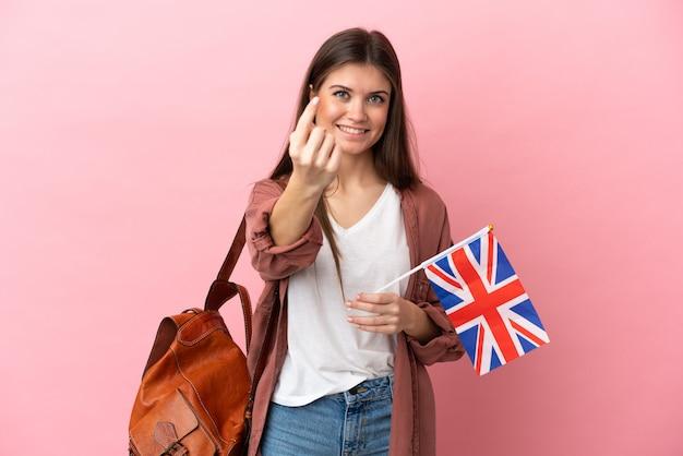 Giovane donna caucasica che tiene una bandiera del regno unito isolata su sfondo rosa facendo un gesto imminente
