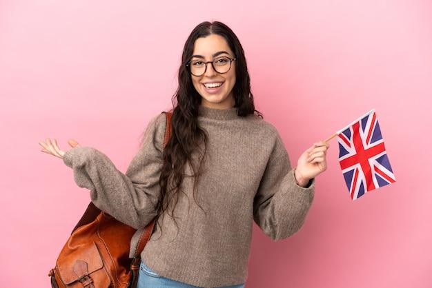 Giovane donna caucasica in possesso di una bandiera del regno unito isolata su sfondo rosa che estende le mani di lato per invitare a venire