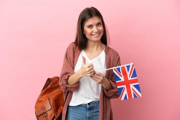 Giovane donna caucasica che tiene una bandiera del regno unito isolata su sfondo rosa che dà un gesto di pollice in alto