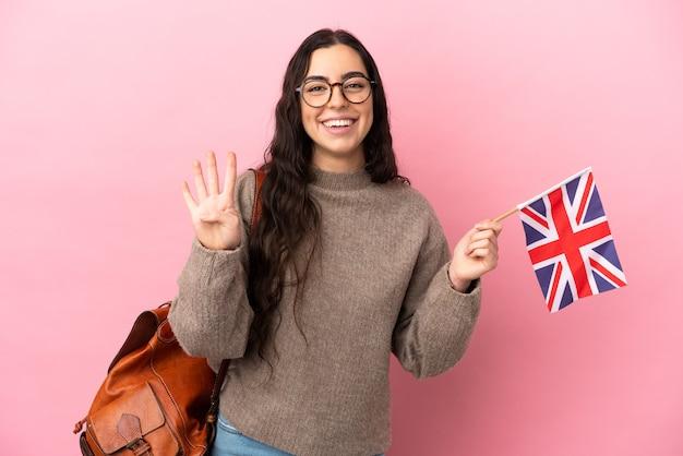 Giovane donna caucasica che tiene una bandiera del regno unito isolata su sfondo rosa felice e contando quattro con le dita