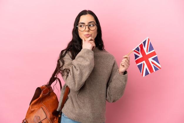 Giovane donna caucasica che tiene una bandiera del regno unito isolata su sfondo rosa che ha dubbi