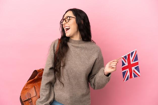 Giovane donna caucasica che tiene una bandiera del regno unito isolata su sfondo rosa ridendo in posizione laterale
