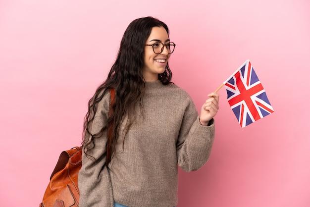 Giovane donna caucasica in possesso di una bandiera del regno unito isolata su sfondo rosa guardando side