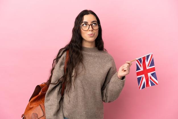Giovane donna caucasica in possesso di una bandiera del regno unito isolata su sfondo rosa e guardando in alto