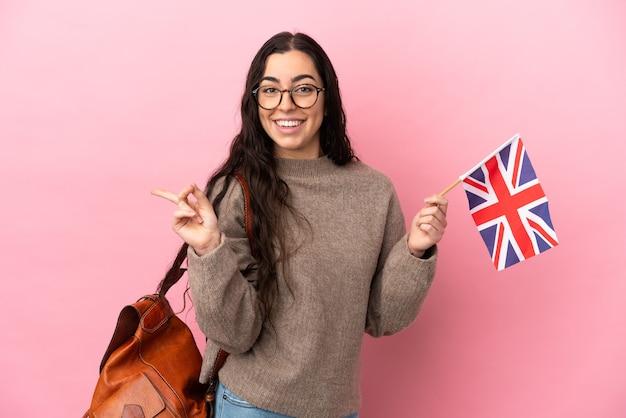Giovane donna caucasica che tiene una bandiera del regno unito isolata su sfondo rosa che punta il dito verso il lato