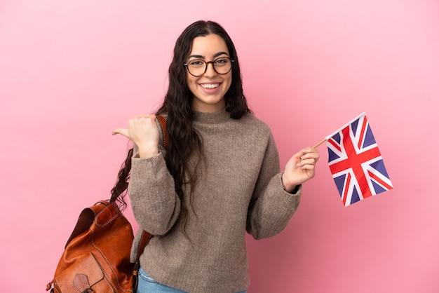 Giovane donna caucasica che tiene una bandiera del regno unito isolata su sfondo rosa che punta al lato per presentare un prodotto