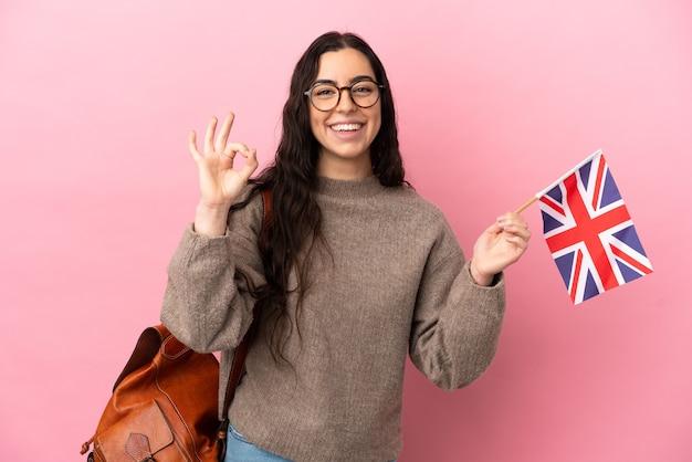 Giovane donna caucasica che tiene una bandiera del regno unito isolata su sfondo rosa che mostra segno ok con le dita