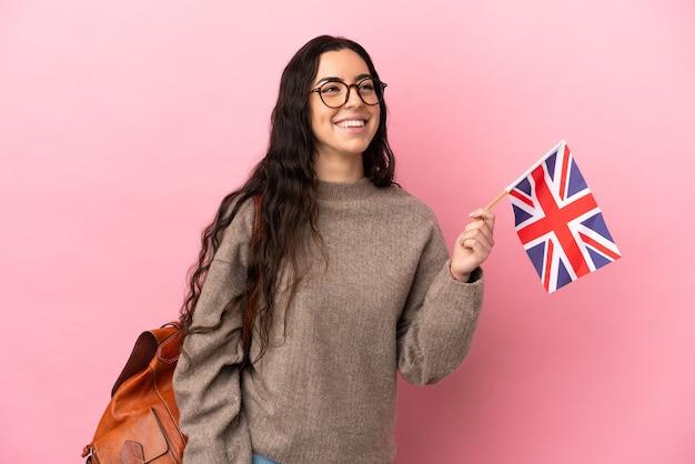 Giovane donna caucasica che tiene una bandiera del regno unito isolata su sfondo rosa pensando un'idea mentre guarda in alto