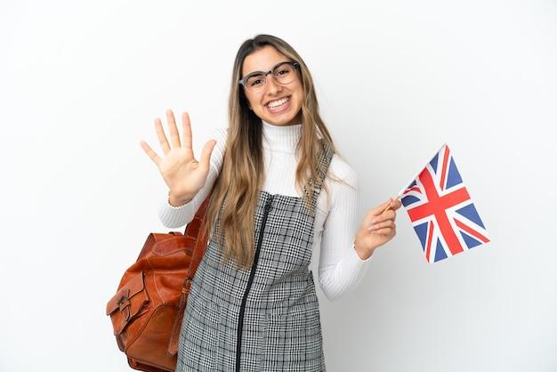 Giovane donna caucasica che tiene una bandiera del regno unito isolata su sfondo bianco contando cinque con le dita