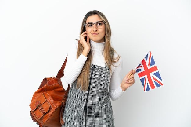 Giovane donna caucasica in possesso di una bandiera del regno unito isolata su sfondo bianco frustrata e che copre le orecchie