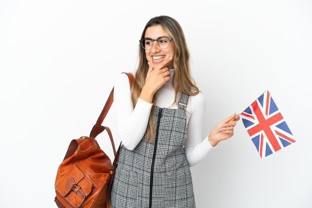 Giovane donna caucasica in possesso di una bandiera del regno unito isolata su sfondo bianco guardando di lato e sorridente