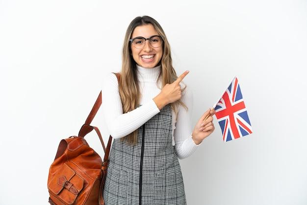 Giovane donna caucasica che tiene una bandiera del regno unito isolata su sfondo bianco che punta al lato per presentare un prodotto