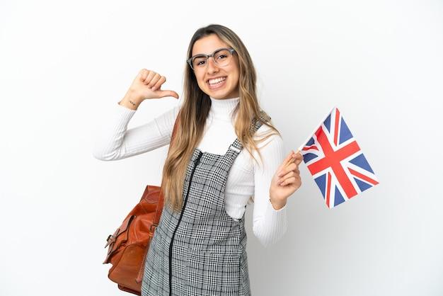 Giovane donna caucasica in possesso di una bandiera del regno unito isolata su sfondo bianco orgogliosa e soddisfatta di sé