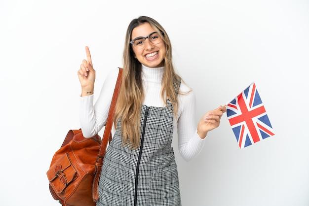 Giovane donna caucasica in possesso di una bandiera del regno unito isolata su sfondo bianco che mostra e solleva un dito in segno del meglio