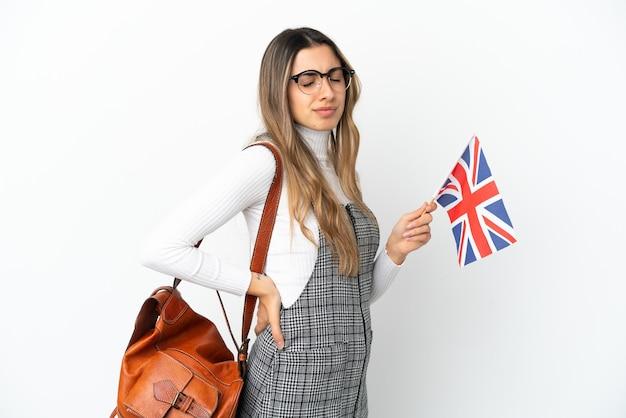 Giovane donna caucasica in possesso di una bandiera del regno unito isolata su sfondo bianco che soffre di mal di schiena per aver fatto uno sforzo