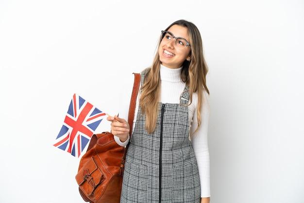 Giovane donna caucasica che tiene una bandiera del regno unito isolata su priorità bassa bianca che pensa un'idea mentre osserva in su