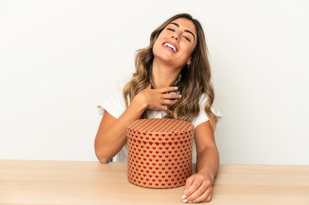 La giovane donna caucasica che tiene una scatola di san valentino isolata ride ad alta voce mantenendo la mano sul petto.