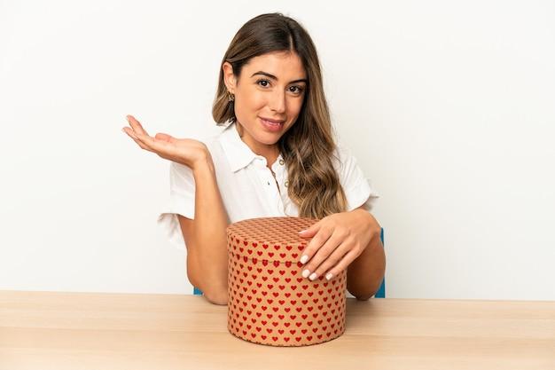 Giovane donna caucasica che tiene una scatola di san valentino isolata che mostra uno spazio della copia su una palma e che tiene un'altra mano sulla vita.