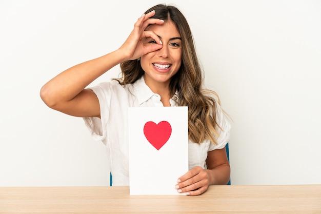 Giovane donna caucasica che tiene una carta di san valentino isolata eccitata mantenendo il gesto giusto sull'occhio.